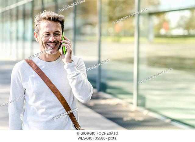 Mature man commuiting in the city, talking on the phone