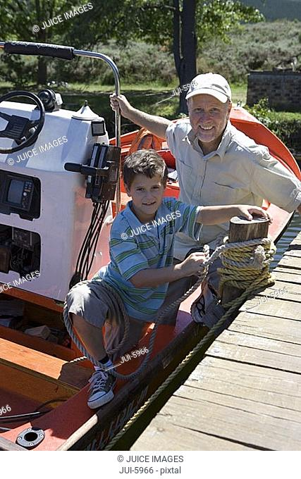 Grandfather and grandson 8-10 sitting in motorboat at lake jetty, boy tying rope to mooring post, portrait