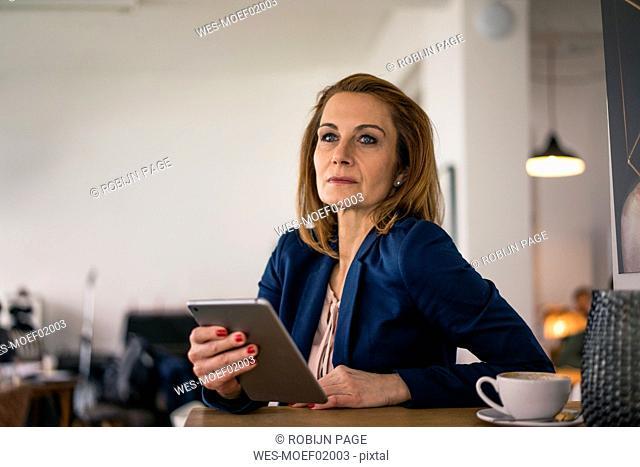 Businesswoman working in coffee shop, using digital tablet