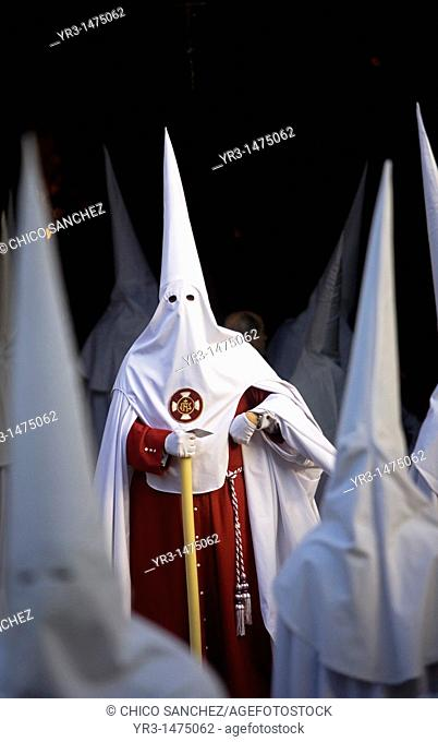 Penitents walk in the Orange Trees Court, Patio de los Naranjos in Spanish, in the Mosque-Cathedral of Cordoba during Easter Holy Week celebrations in Cordoba