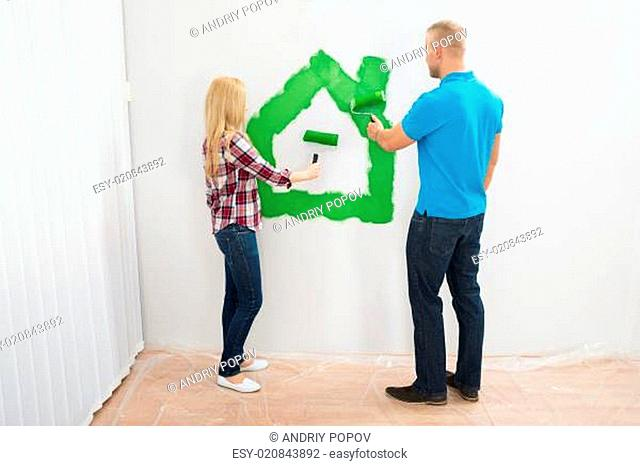 Couple Making Home With Paint On The Wall
