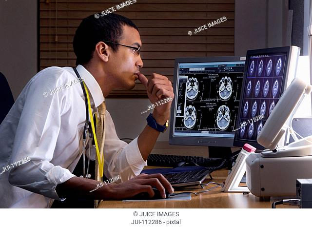 Focused doctor reviewing digital brain scan in doctor