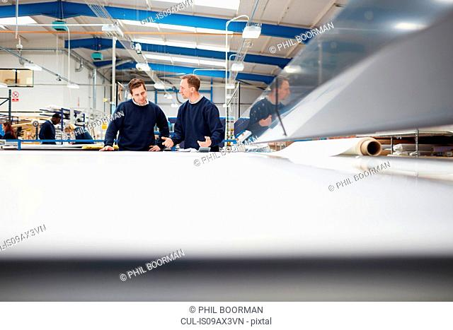Manager mentoring worker on production line in roller blind factory