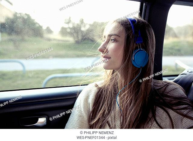 Young woman with windswept hair in a car wearing headphones