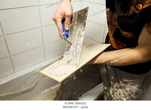 Close up of a builder, tiler spreading adhesive on the back a tile