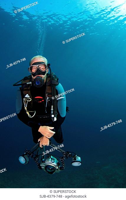 An underwater photographer doing a decompression stop, or deco stop, a halt in accent from a dive to safely purge absorbed inert gases and avoid decompression...