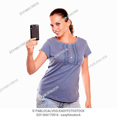 Smiling young woman taking a photo with cellphone on blue shirt standing over white background