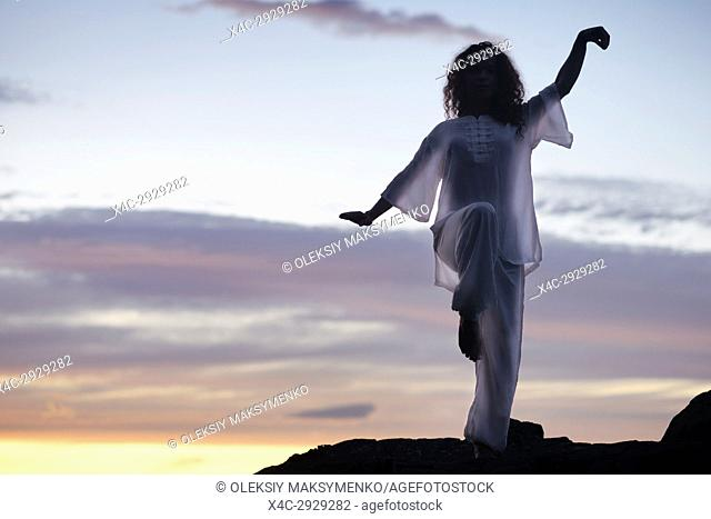 Woman practicing Tai Chi outdoors, dark silhouette in white uniform over sunset skies