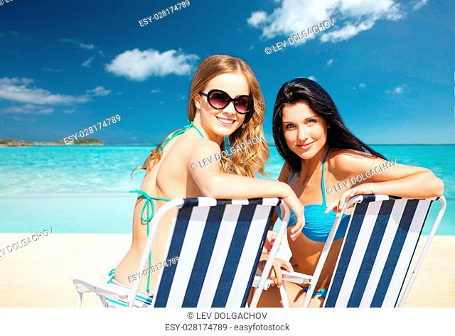 summer holidays, people, leisure, vacation and travel concept - happy women sunbathing in chairs over exotic tropical beach background