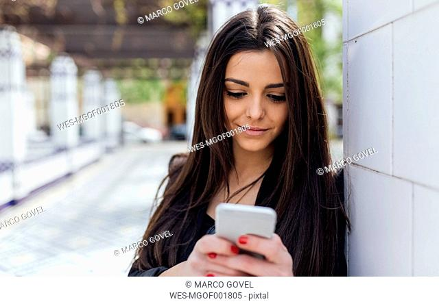 Young beautiful woman sending a message with the smartphone