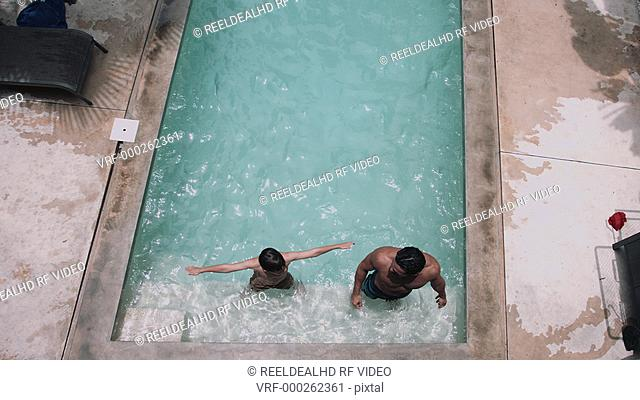 Man with son jumping while enjoying in swimming pool