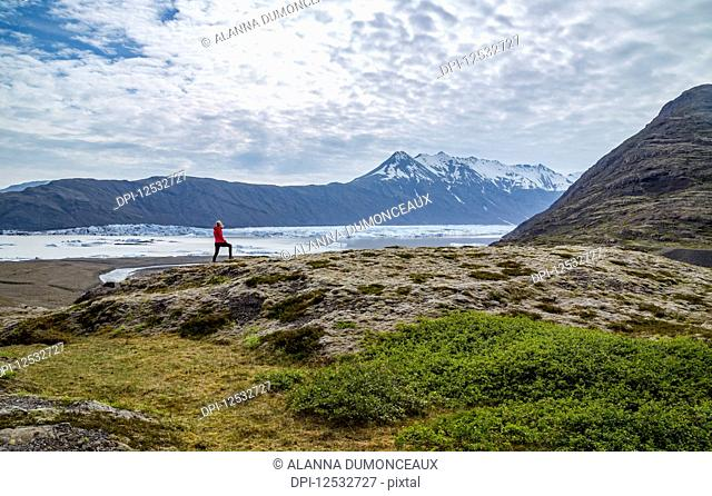 A female hiker walks along the edge of a hill on the trail above a glacier lake and mountain viewpoint in Southern Iceland, Vatnajokull National Park; Iceland