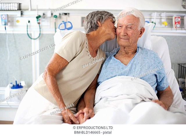 Wife kissing husband in hospital bed