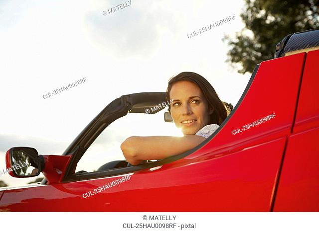 Women sitting in her electric sports car