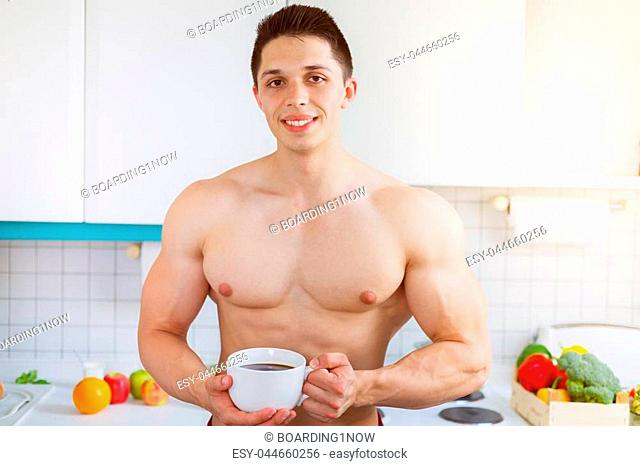 Bodybuilder young man shirtless drinking coffee in the kitchen morning smiling