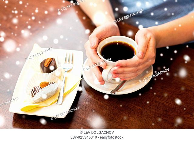 drinks, people and lifestyle concept - close up of woman hands holding cup with hot black coffee and dessert over snow