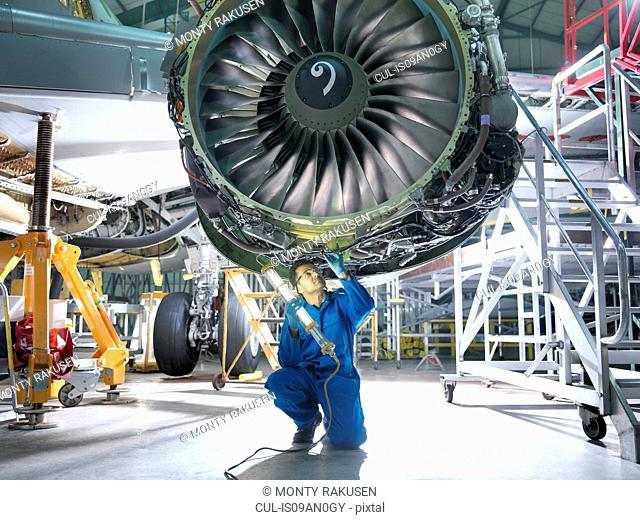 Engineer inspecting jet engine in aircraft maintenance factory