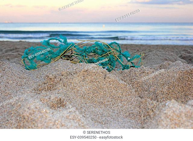 Worn out green blue rope nylon fishing net jumbled up and washed ashore in front of a sandy atlantic coast beach at sunset emphasizing trash's endangerment to...