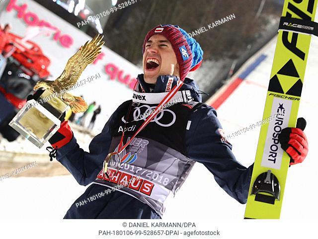 Kamil Stoch of Poland celebrates holding the trophy in his hand after his final jump at the Four Hills Tournament in Bischofshofen, Austria, 6 January 2018