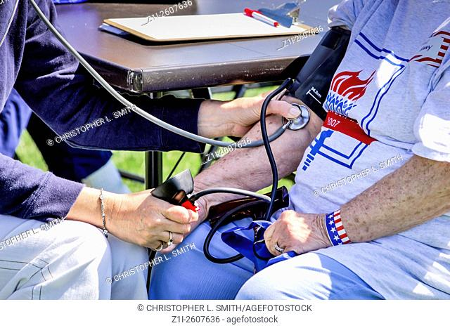 Senior person having their Blood pressure tested at an outdoor medical clinic