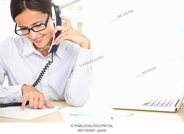 Female company worker with glasses talking on the phone while smiling in the office - copyspace