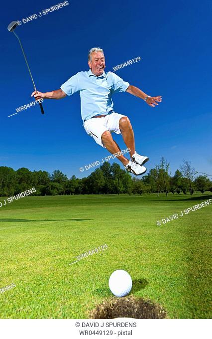 A senior citizen leaps for joy as golf ball heads towards success