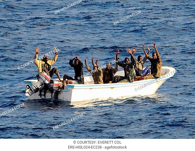 Seven suspected pirates with hands raised on orders of a U.S. Naval counter-piracy search and seizure team in the Gulf of Aden. Feb. 11 2009