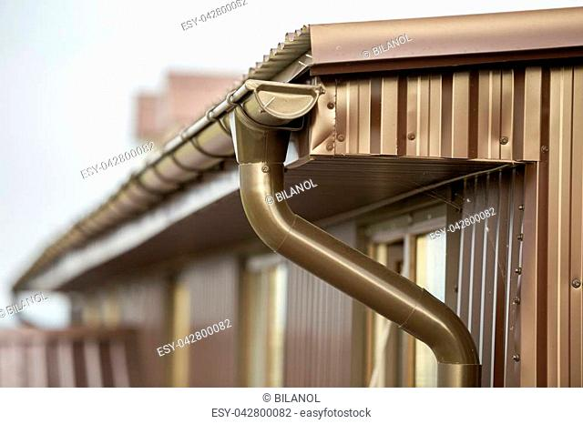Close-up detail of cottage house corner with metal planks siding and roof with steel gutter rain system. Durability, professional construction