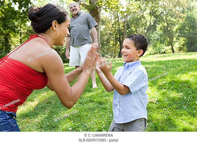 Mother playing pat a cake with son in park