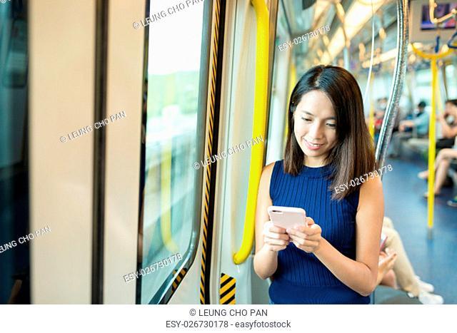 Woman sending text message inside train compartment