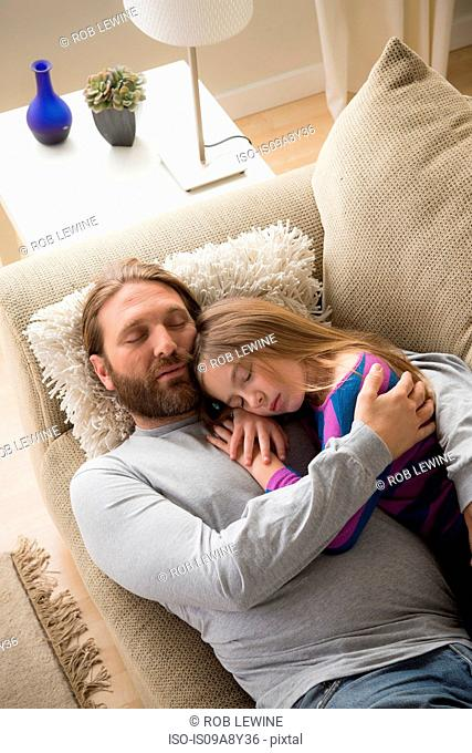 Father and daughter sleeping on couch