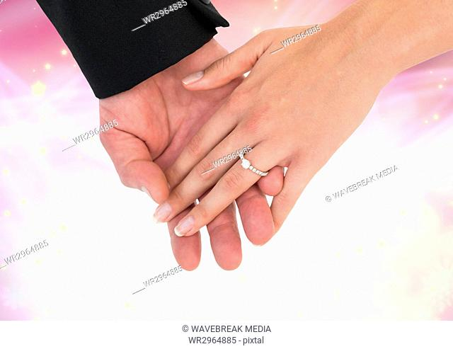 Hands holding together wedding engagement ring with sparkling light bokeh background