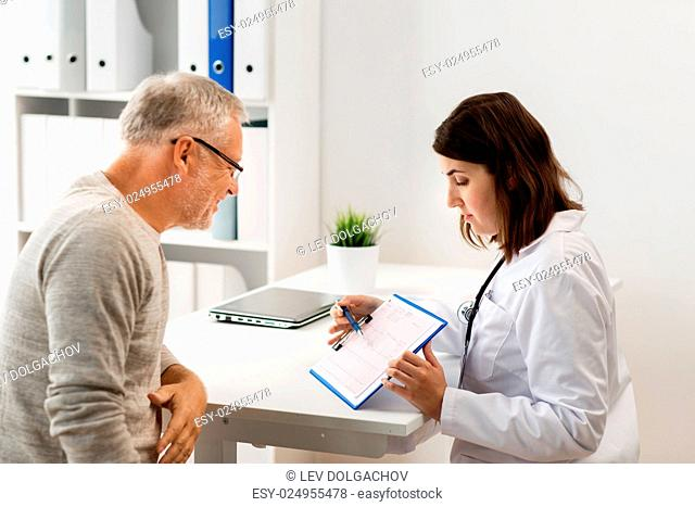 medicine, age, health care, cardiology and people concept - senior man and doctor with cardiogram on clipboard meeting in medical office at hospital