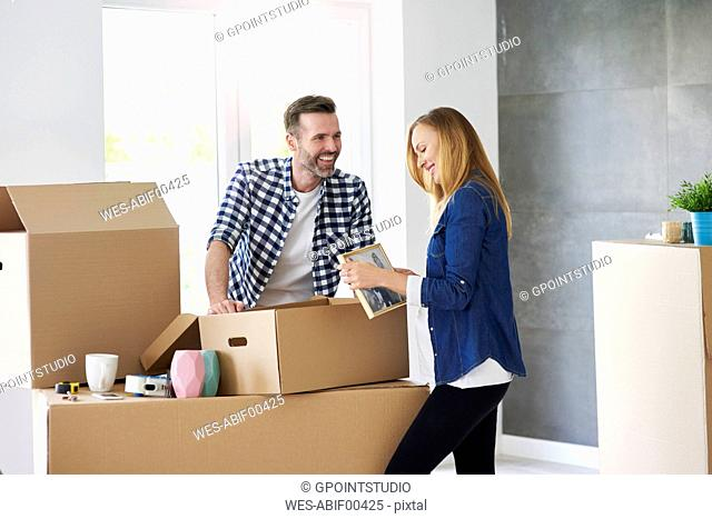 Couple moving into new flat packing cardboard boxes