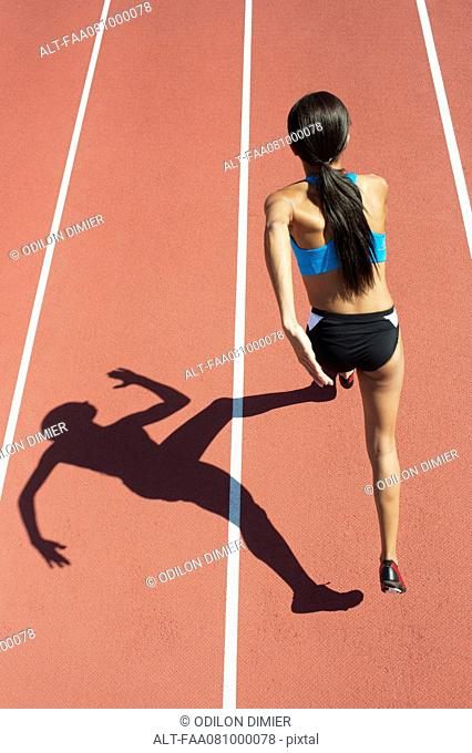 Female athlete running on track, focus on shadow