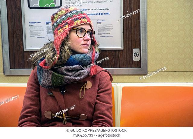 New York City, USA. Young, brunette woman commuting by subway from JFK Airport towards Bushwick, Brooklyn