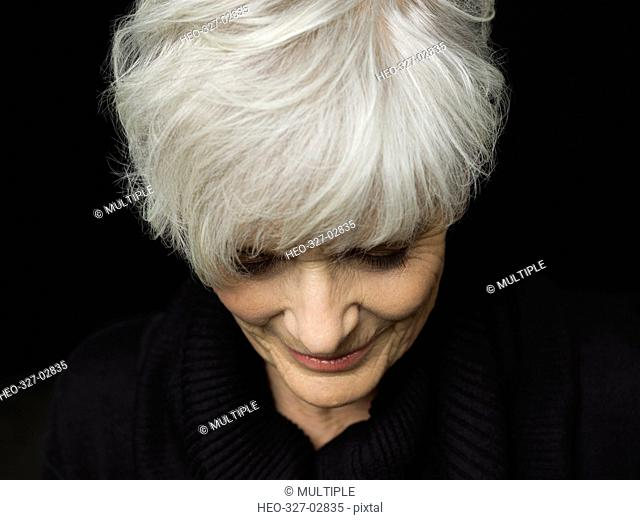 Close up portrait senior woman with short white hair looking down against black background