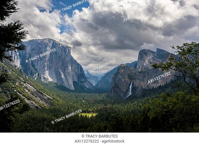 Clouds move over Yosemite Valley, with Bridalveil Falls on the right and El Capitan on the left, Yosemite National Park; California, United States of America