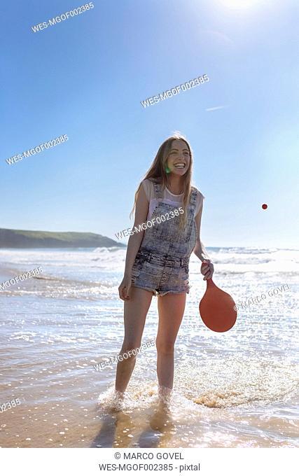 Happy teenage girl playing beach paddles on the beach