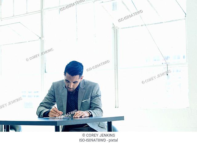Businessman writing notes on table by office window