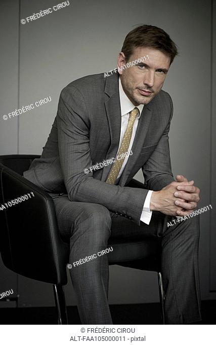 Businessman sitting in chair, portrait