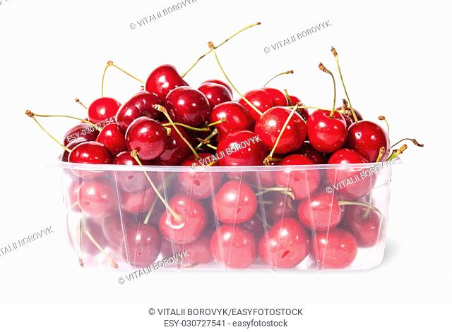Red juicy sweet cherries in a plastic tray isolated on white background