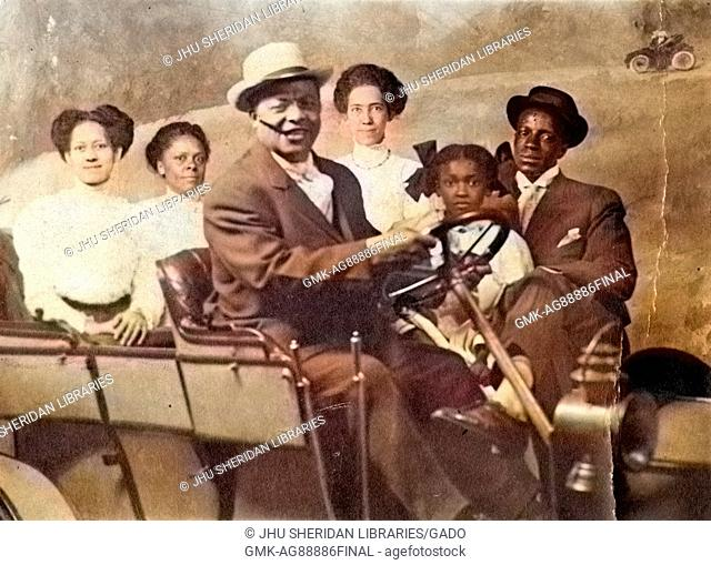 Portrait of African-American family, with automobile, in photographic studio, 1930. Note: Image has been digitally colorized using a modern process