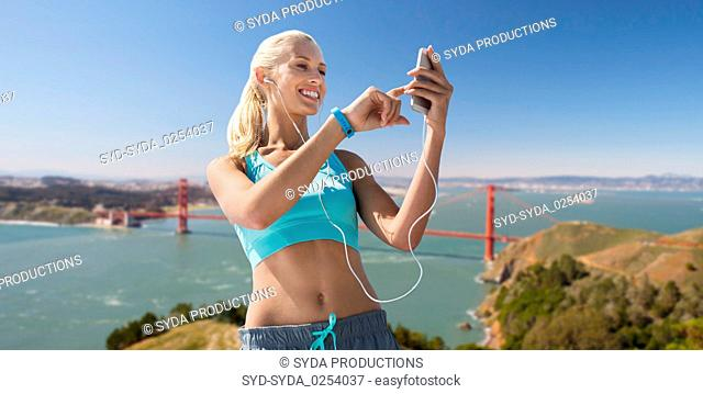 woman with smartphone and earphones doing sports