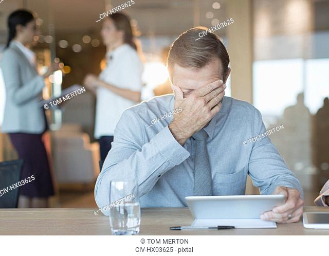 Tired, stressed businessman using digital tablet in conference room