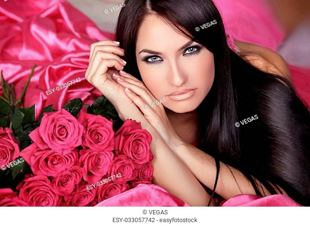 Beauty portrait of brunette girl with pink Roses lying on the bed. Beautiful Woman with Blue Eyes and long black hair. Passion