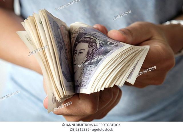 Woman counts British Pound Sterling