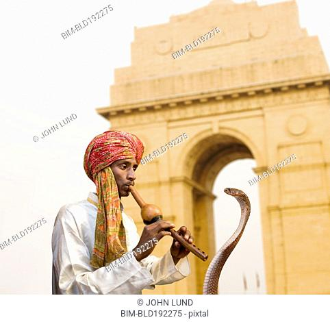 Asian snake charmer playing flute