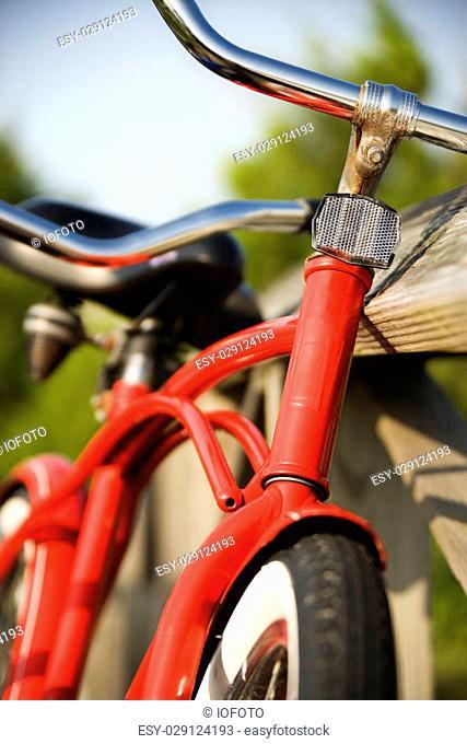 Image of red bike leaning against railing of boardwalk