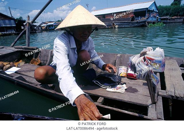 Mekong delta. Man in shallow boat. Lottery tickets for sale. Bundles of currency,banknotes. Houseboat. DwellingsGames,board games